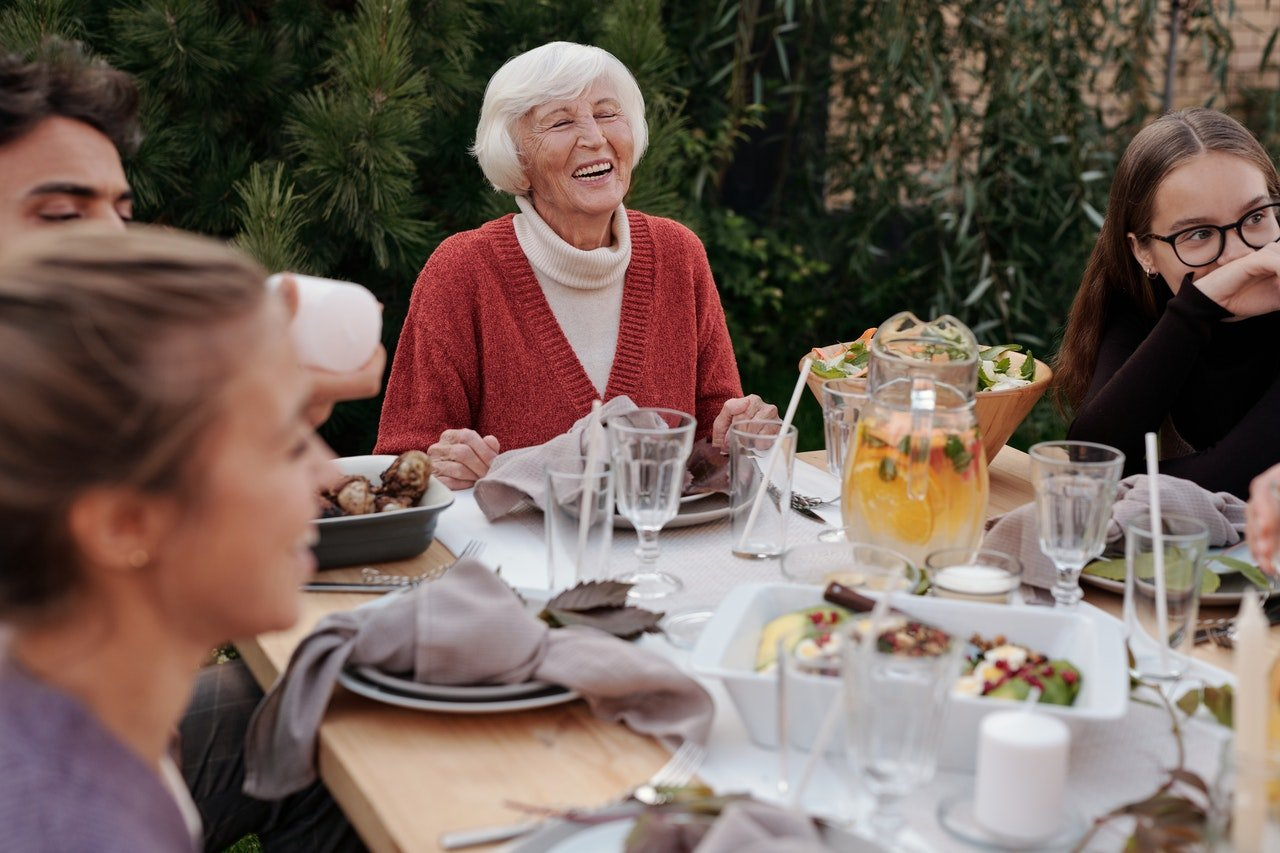 elderly woman laughing eating a meal with friends and family