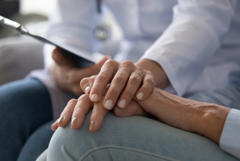young woman doctor holding hand of senior grandmother patient
